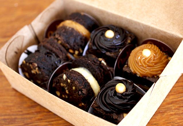 50 Mini Brownies com pingos de brigadeiro em cima na caixeta de papel de R$100 por R$69,90