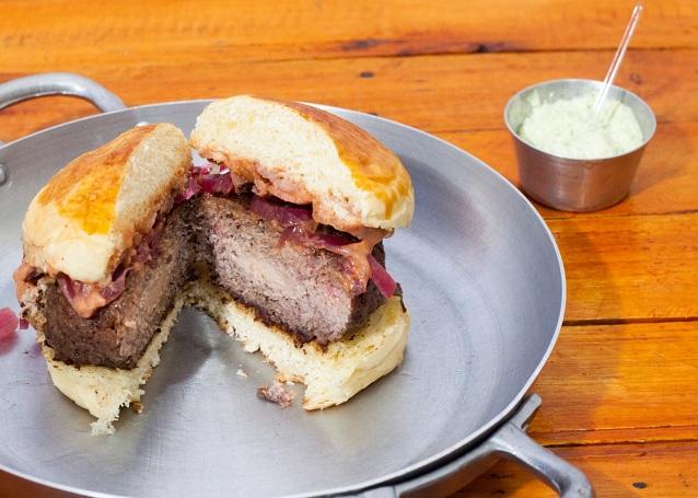 1 Hambúrguer Tiana (pão brioche artesanal, burger de costela de 250g com recheio de polenguinho, picles de cebola roxa, bacon, molho rosé picante) por apenas R$17,50